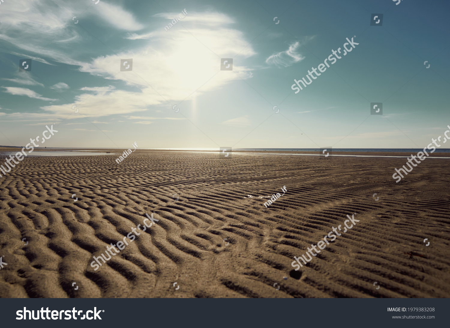 the surface of the sand against a blue sky with white clouds, upward view.  #1979383208