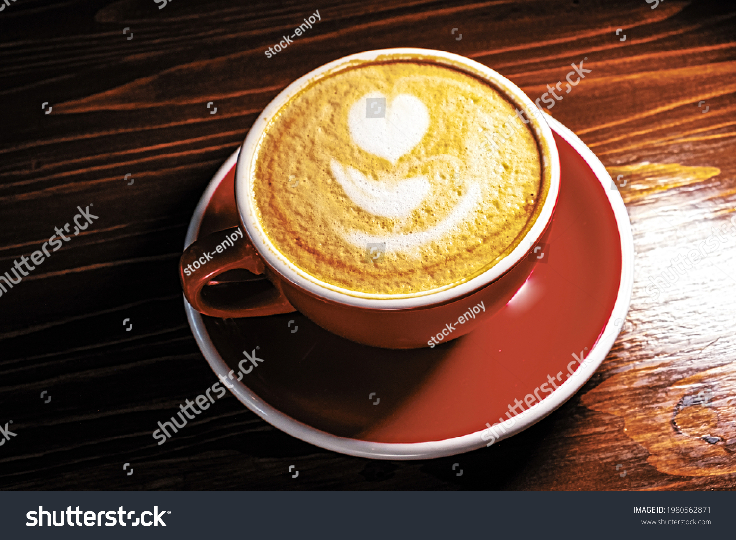 Red cup of latte coffe with froth art on top, half in dark above view on wooden desk