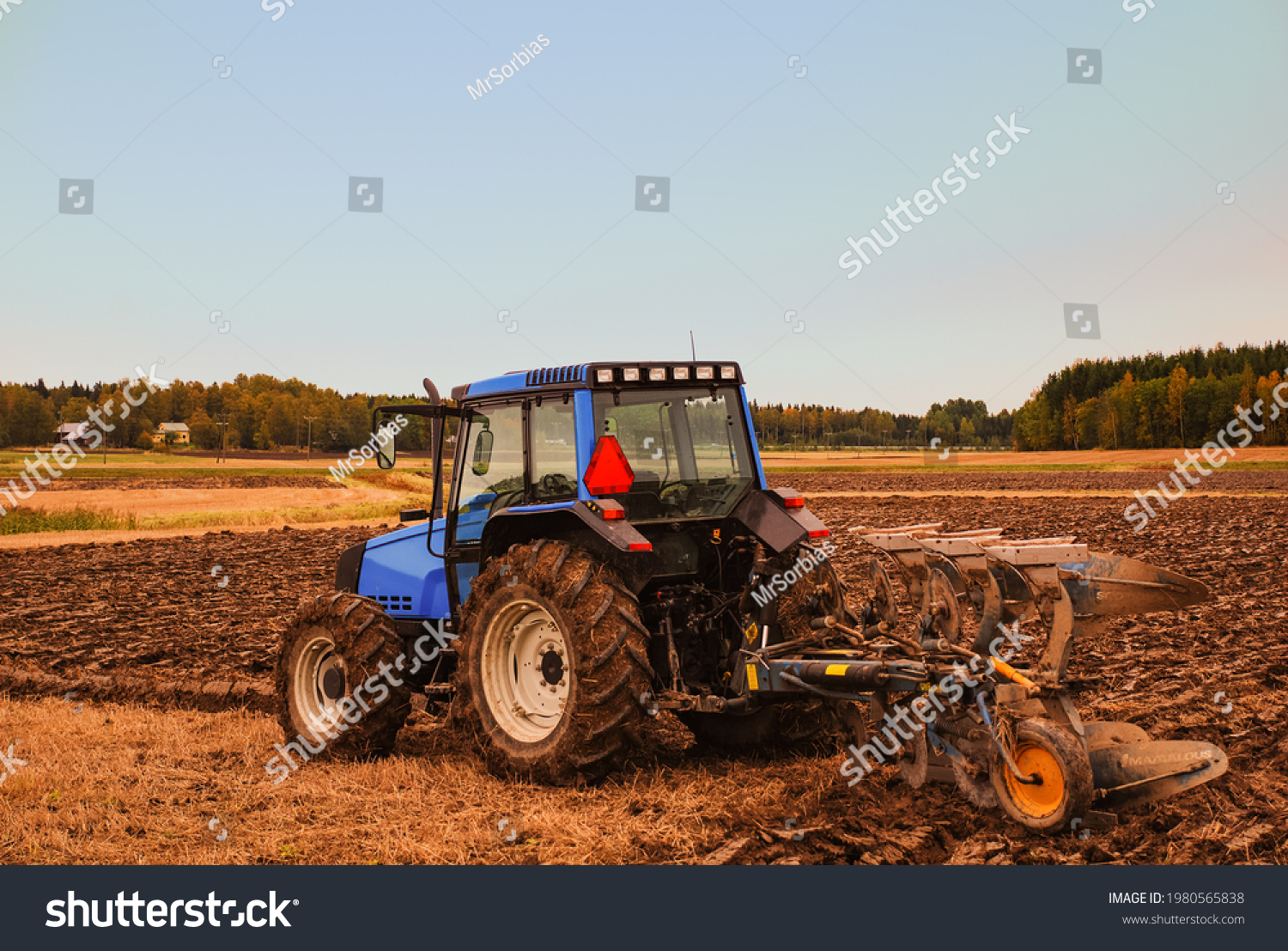 stock-photo-tractor-plowing-field-on-a-c