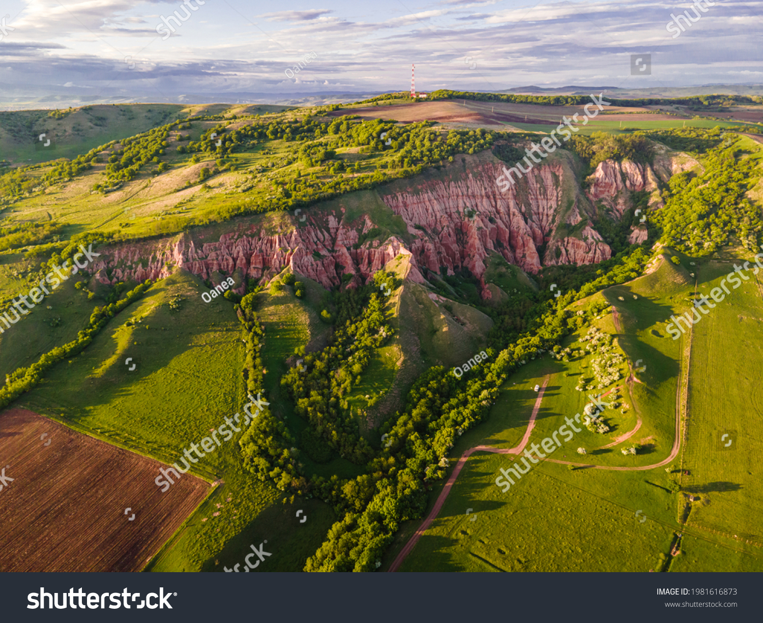 Aerial photography of the Red Ravine located in Romania, Alba county. Photo taken from a drone at sunset in spring season. Drone shot of a canyon formation from a high angle