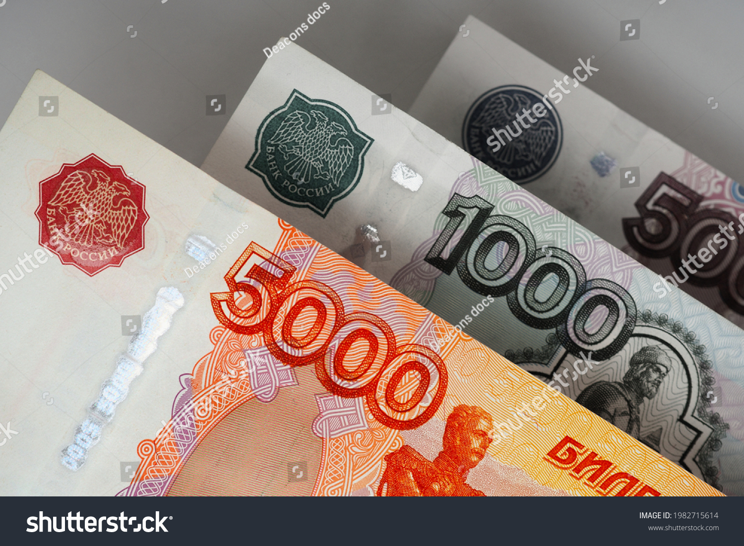 Russian banknotes 5000, 1000 and 500 rubles close up. Bright expressive illustration about economy and money of Russia. Nearest bill is highlighted in vivid color, other notes are pale. Macro #1982715614