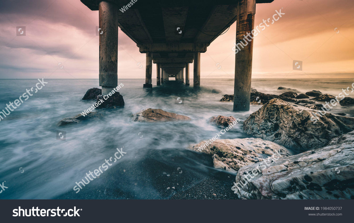 A bottom view of a rocky coast boarding an old wooden pier during a dramatic sunset #1984050737