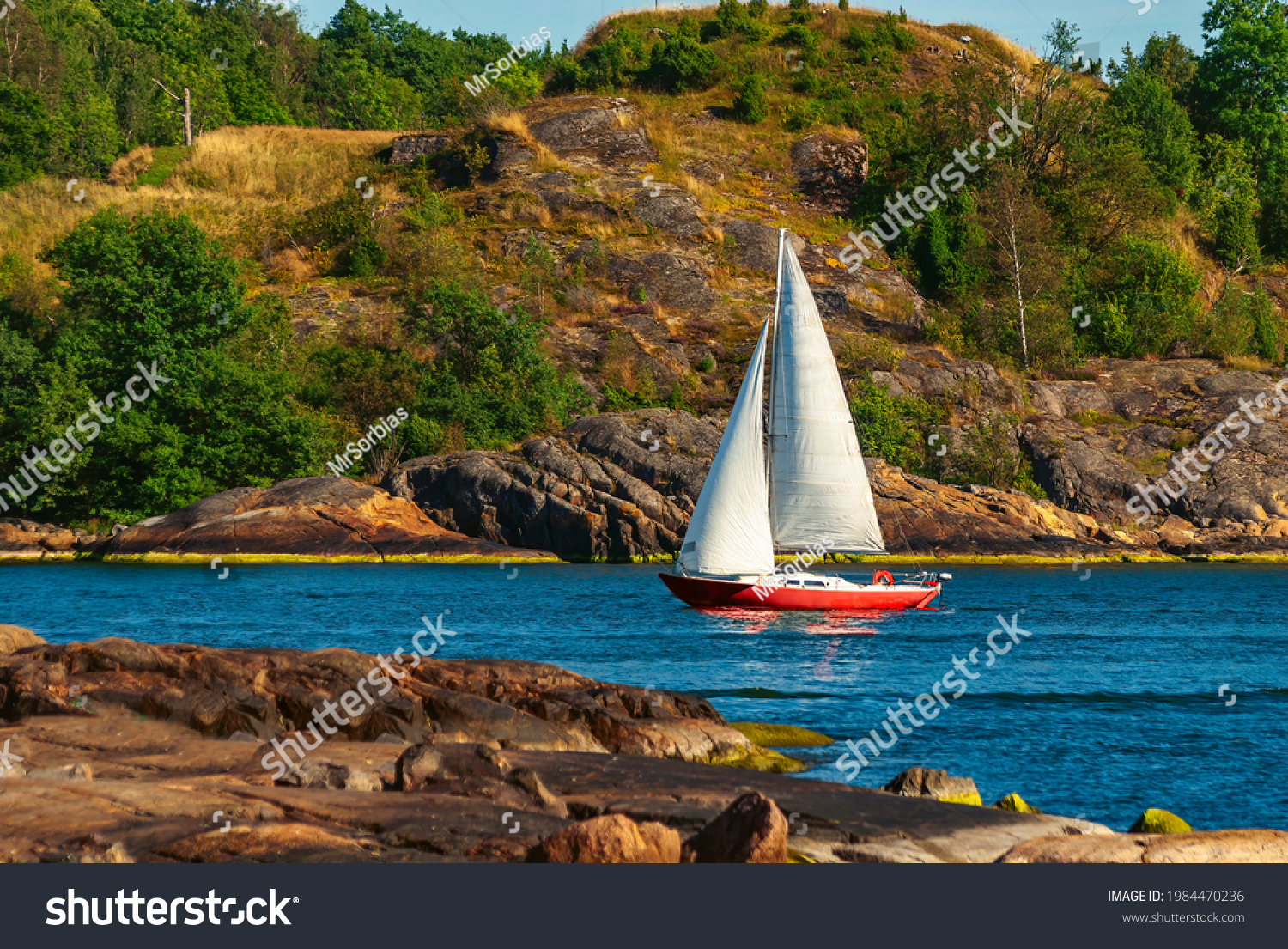Sail boat sailing between two islands in Finnish gulf near the Suomenlinna