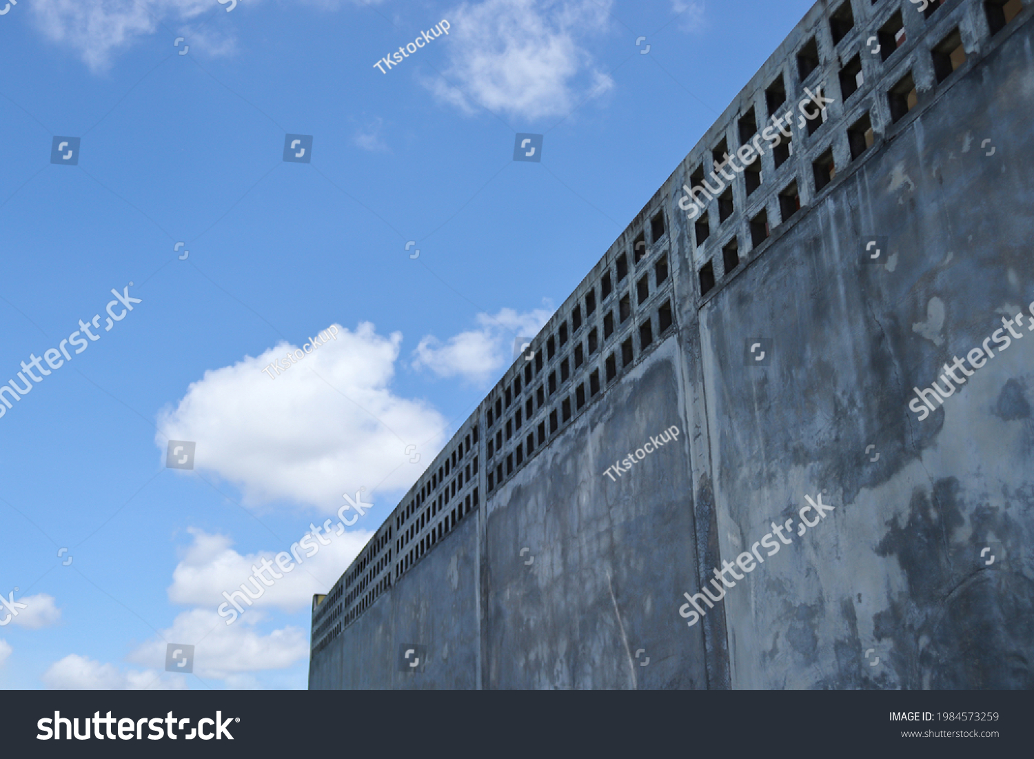 The high wall fence line is made of cement. with a background of sky and clouds during daytime. Construction of walls to create boundaries. #1984573259