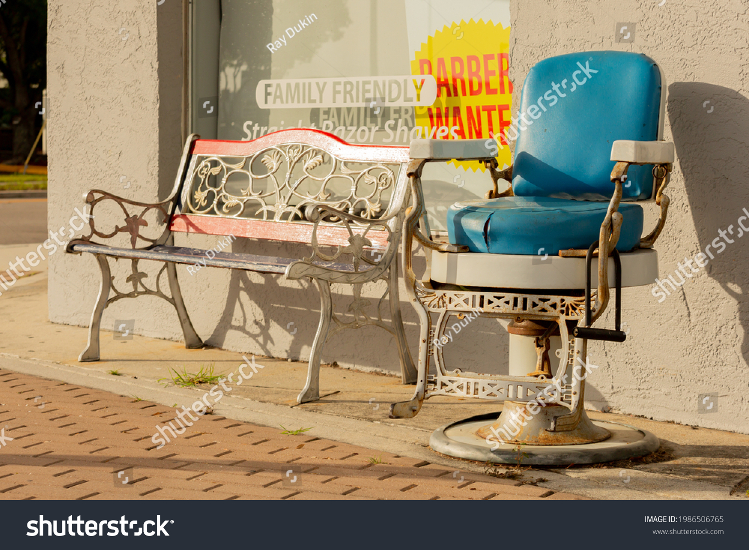 Antique style barber chair next to a bench on a sidewalk