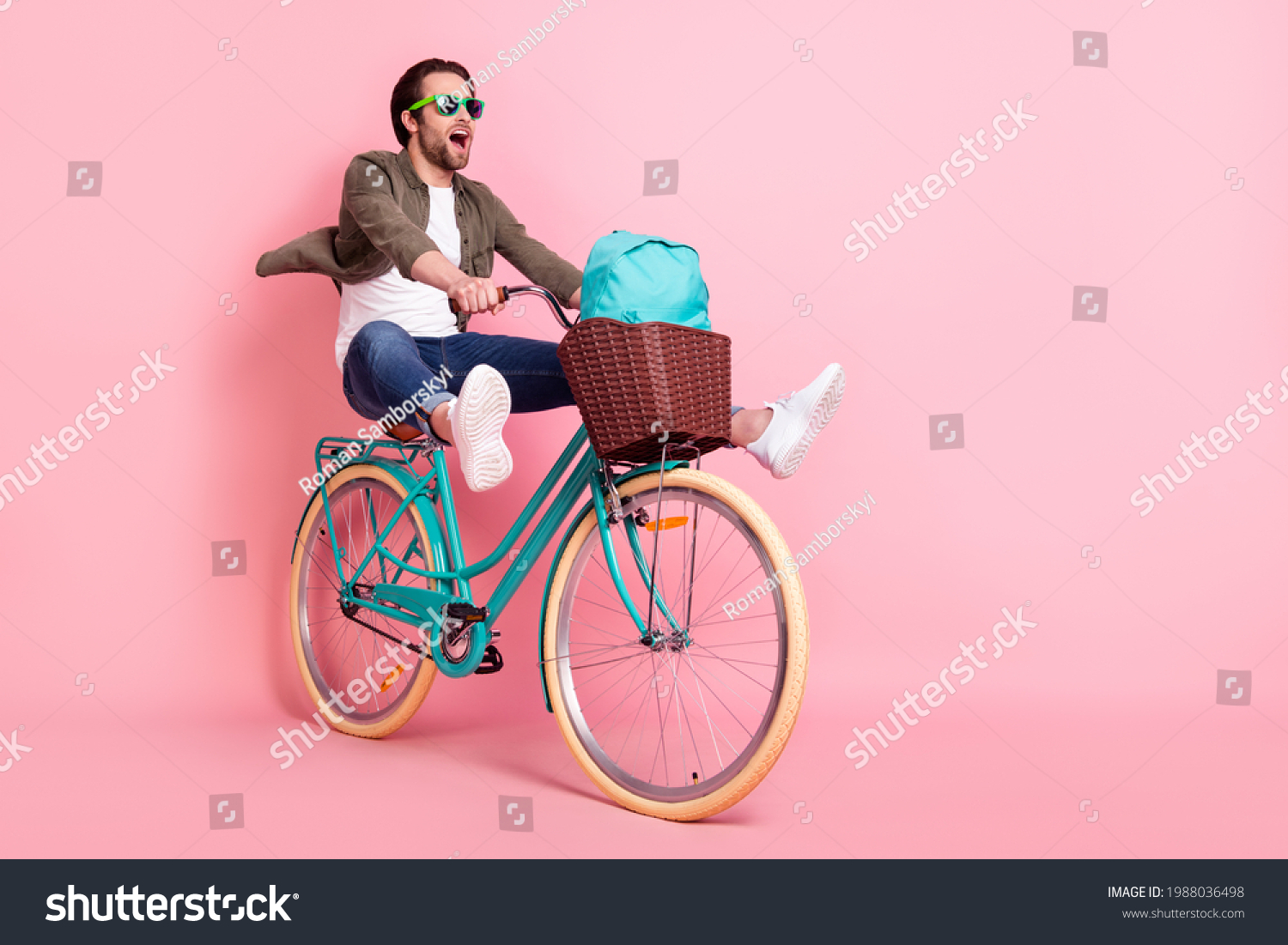 Photo of sweet cute guy dressed brown shirt dark eyeglasses riding bike backpack looking empty space isolated pink color background #1988036498