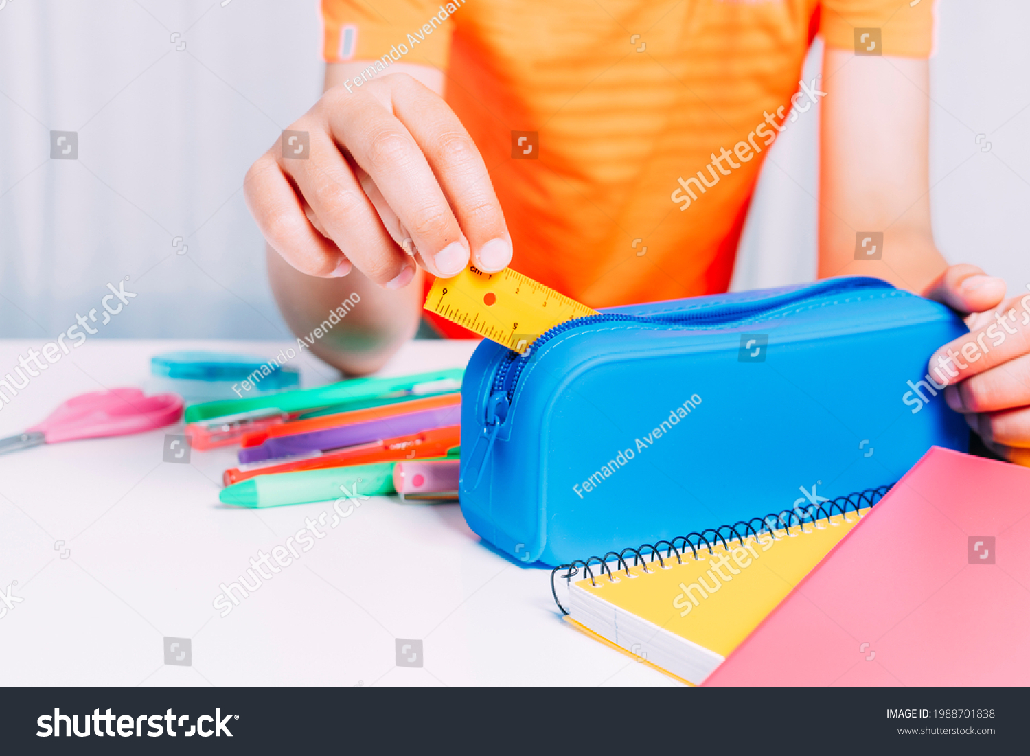 Boy keeping inside his blue pencil case all a small ruler and pencils, pencils, scissors, etc. Colorful notebooks on white table. Back to school concept #1988701838