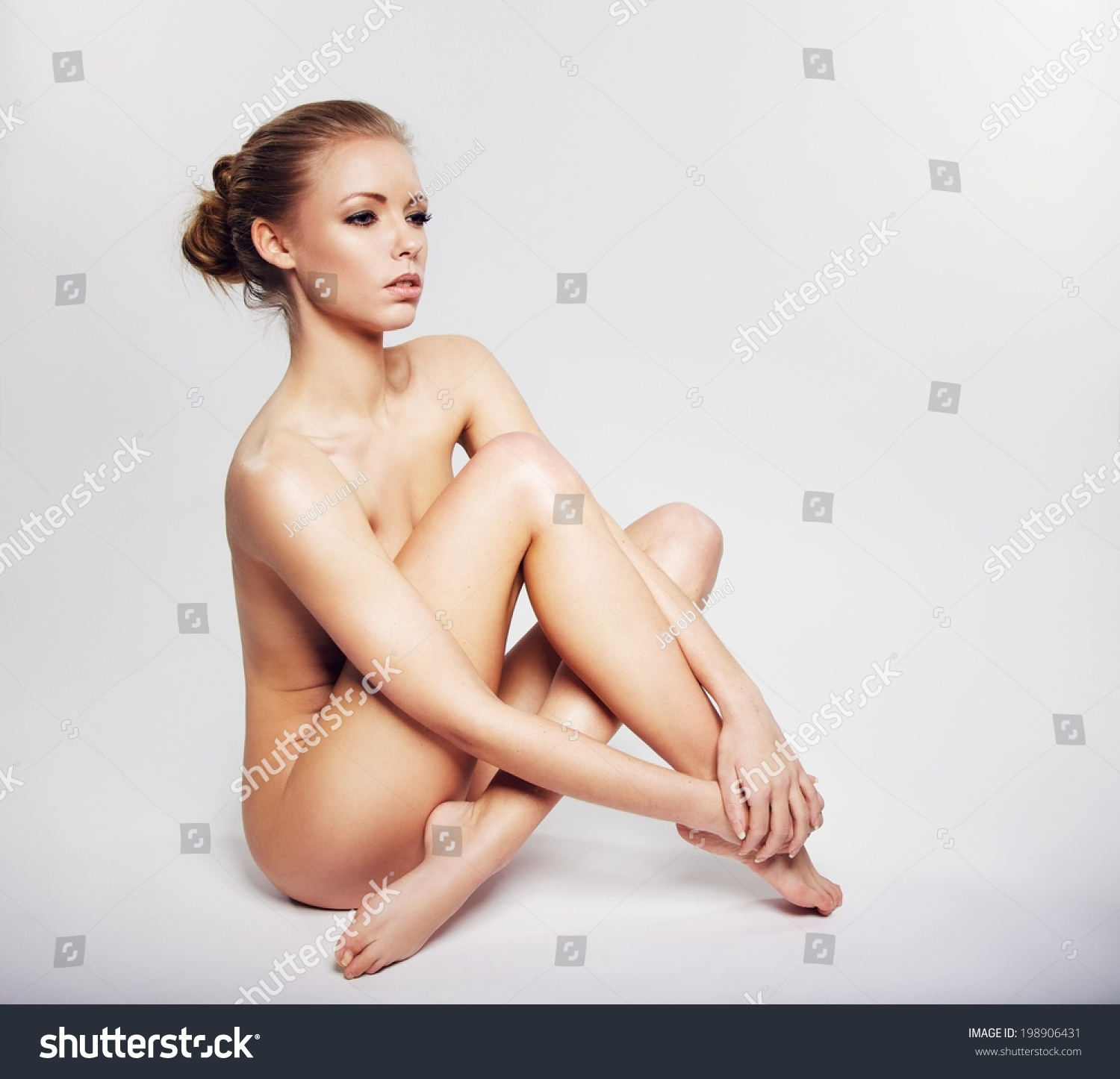 nude young woman sitting on floor stock photo (royalty free