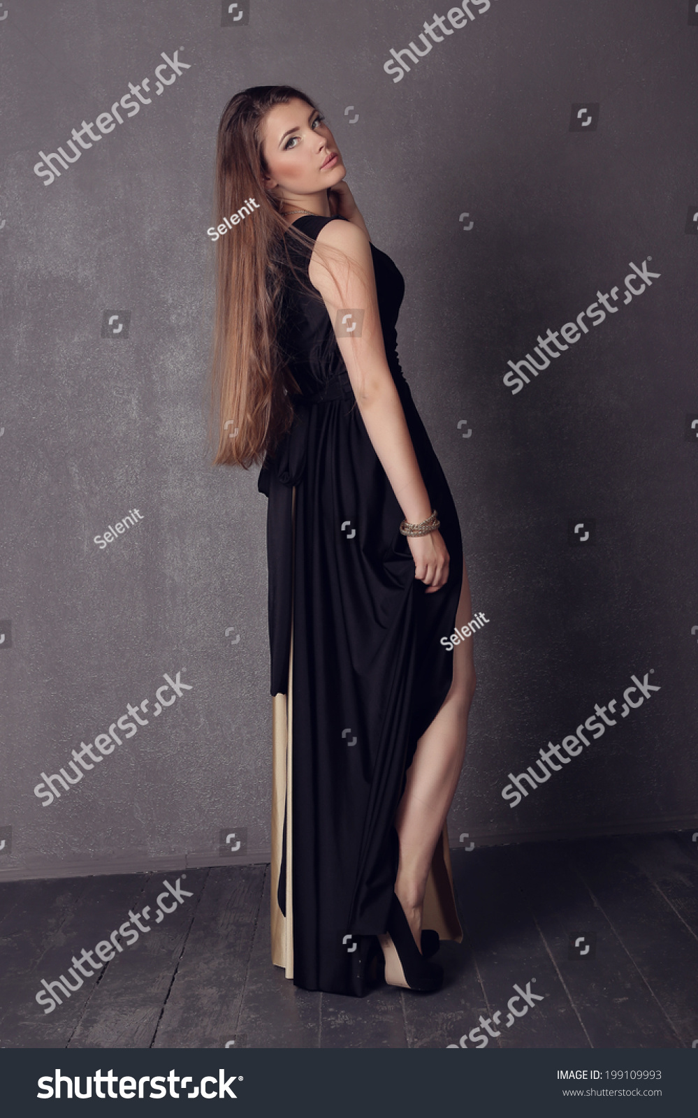 30293492b3 Young brunette lady in black ang golden dress posing on grey background.  Fashion studio shot