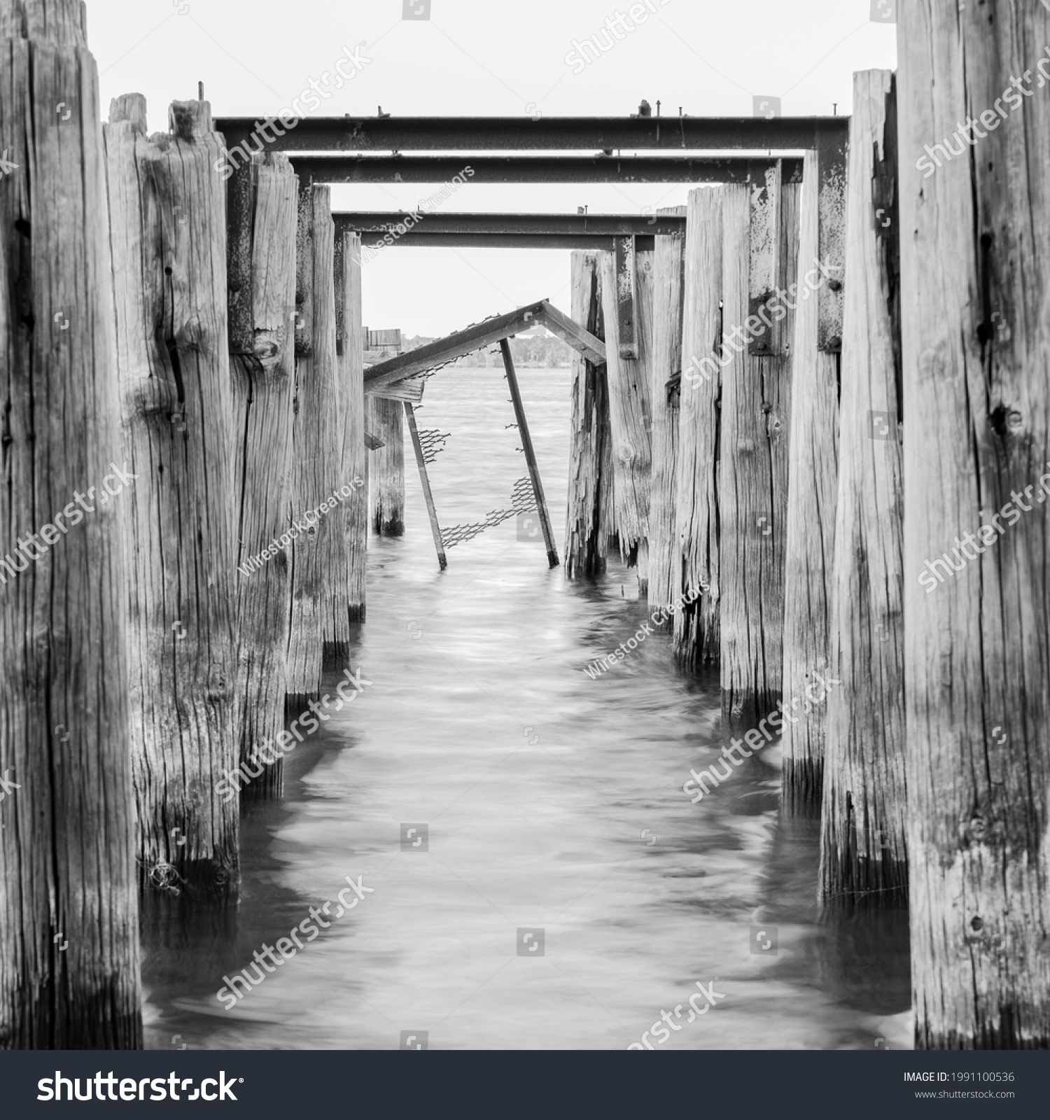 A grayscale of weathered columns of a wooden pier in the sea on background of the sky #1991100536