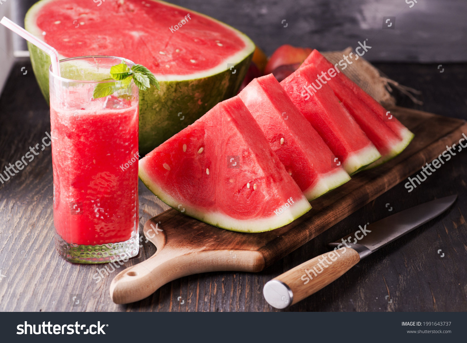 Fresh watermelon juice with ice in a glass. Slices of watermelon on the table.Fresh watermelon juice with ice in a glass. Slices of watermelon on the table. #1991643737
