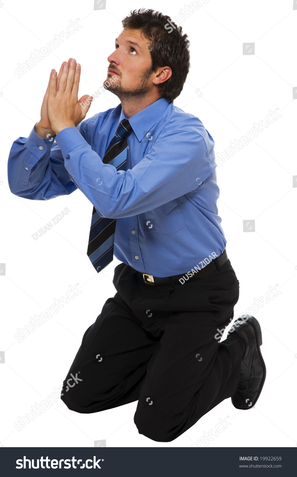 Young Business Man On His Knees Praying Stock Photo
