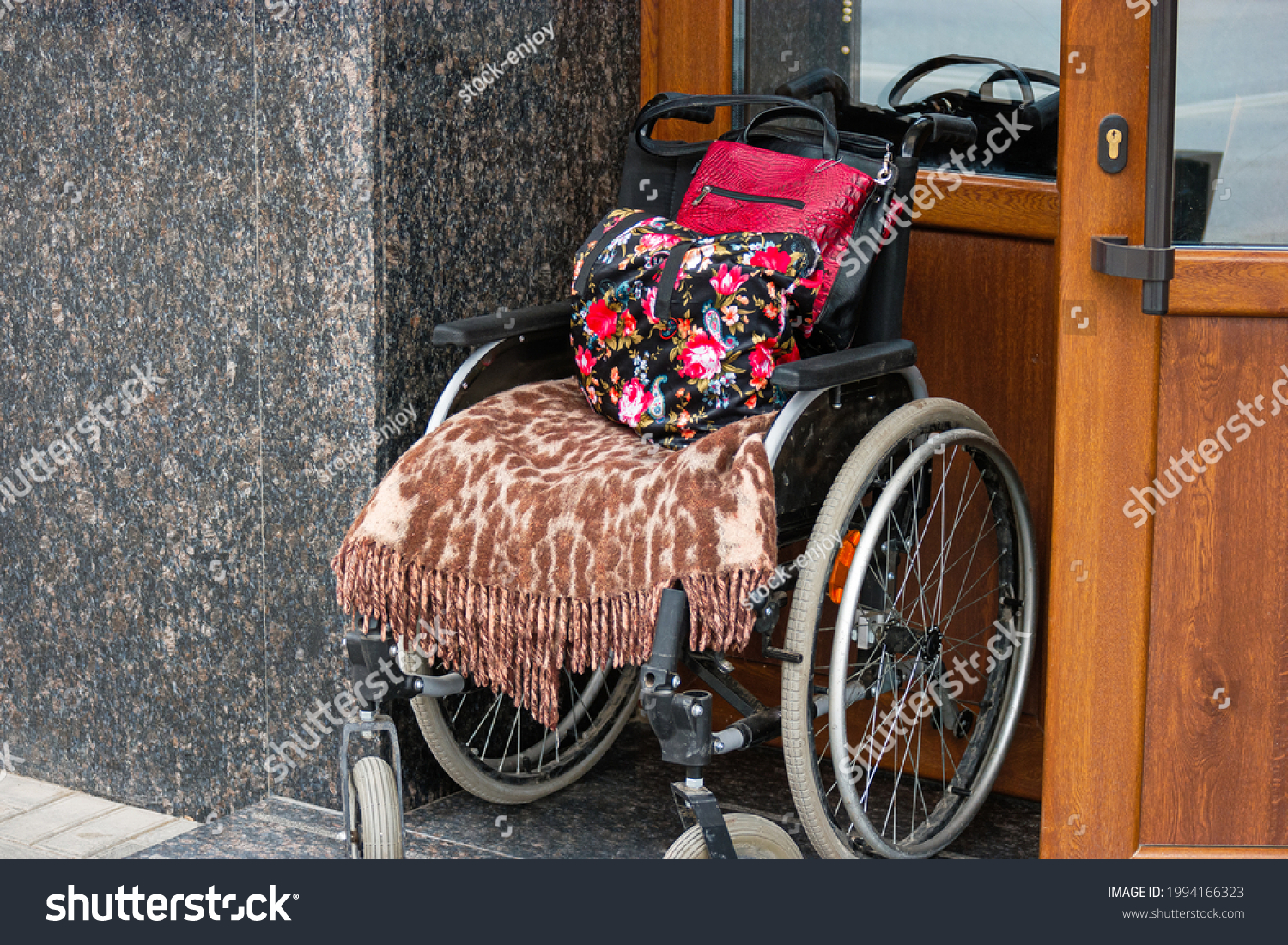 Wheelchair stands at the door of the state office in Russia. Black and red stroller with brown and white textile