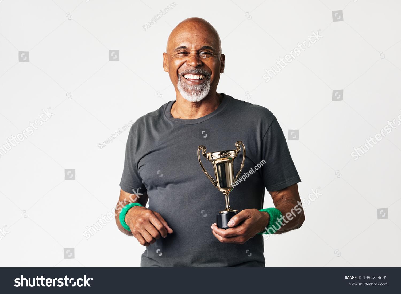 Sporty senior man holding a golden trophy #1994229695