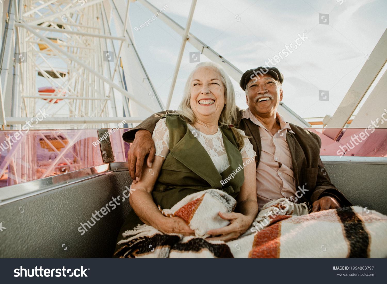 Cheerful senior couple enjoying a Ferris wheel by the Santa Monica pier #1994868797