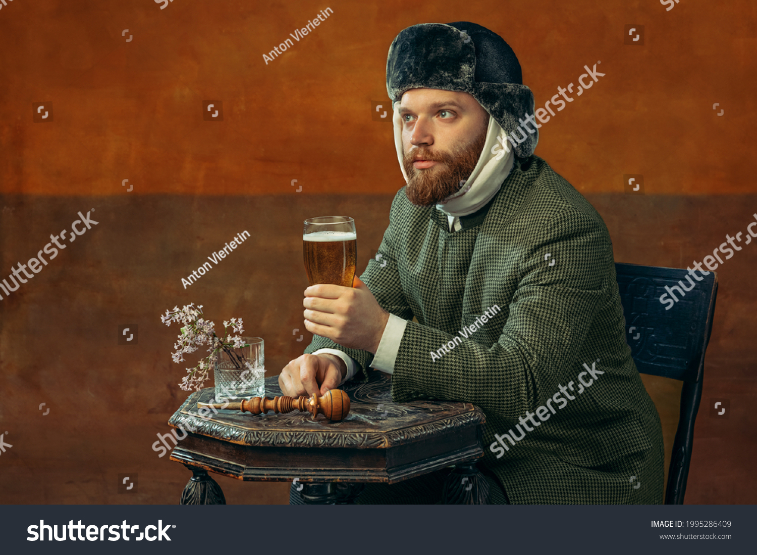 Drinking beer. Portrait of red headed and bearded man playing famous artist Van Gogh isolated on dark orange bacground. Concept of art, eras comparison, fashion. imitation, humor, ad. Bandaged ear. #1995286409