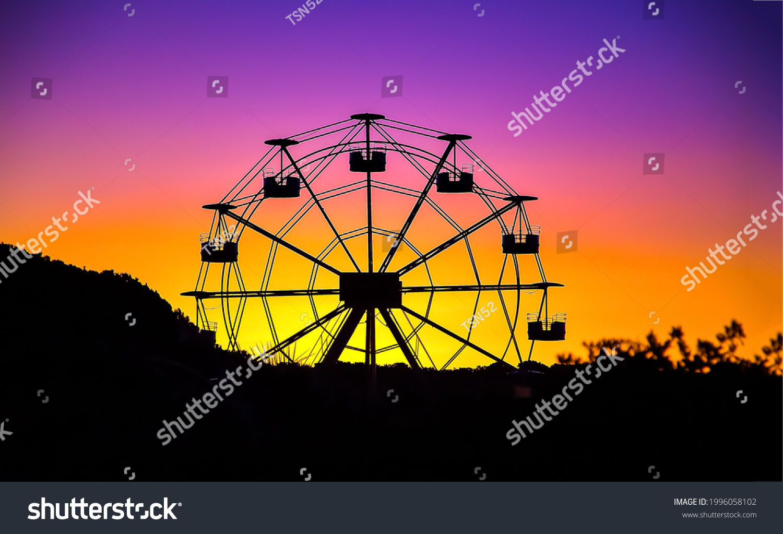 Ferris wheel on sunset background. Sunset ferris wheel silhouette. Ferris wheel silhouette at sunset. Sunset ferris wheel #1996058102