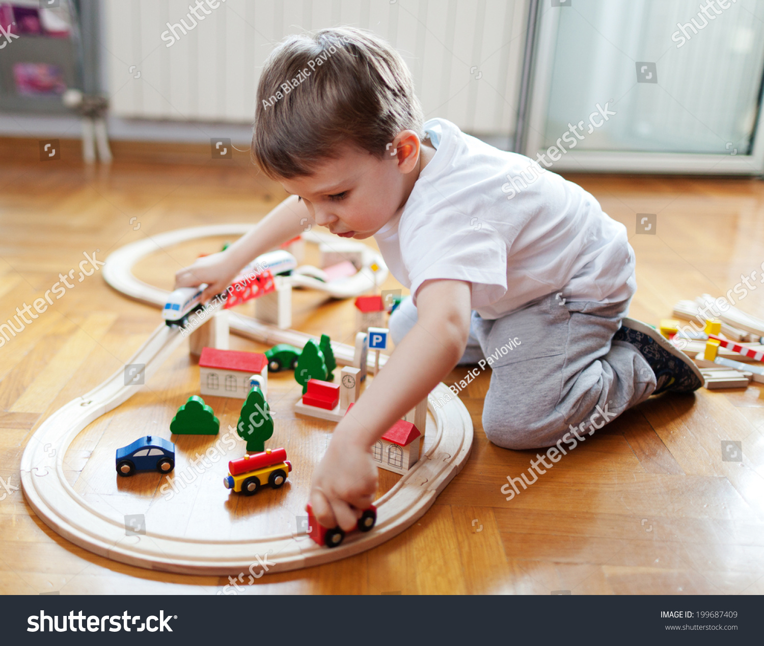 Learning Toys For Autistic Boys : Little boy playing with wooden train set stock photo
