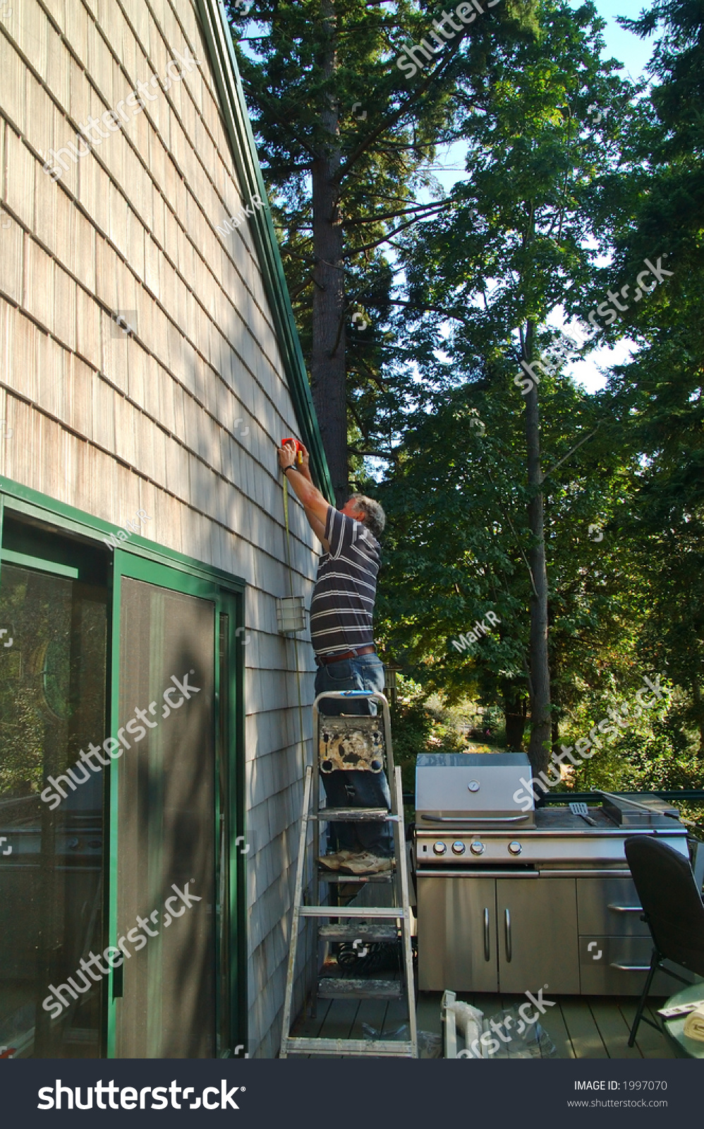 A Retired Man Putting Up An Awning On The Sliding Glass ...