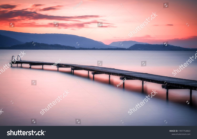 Sunset over the mountain lake pier. Sunset lake pier. Lake pier at sunset. Mountain lake pier at sunset #1997754863