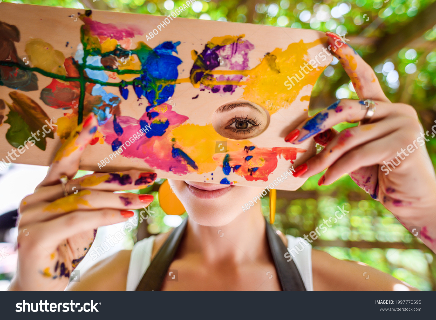 Playful portrait of a young gorgeous female artist painter covered in paint, looking and smiling at camera through her painter's palette. Creativity and individuality concept. #1997770595