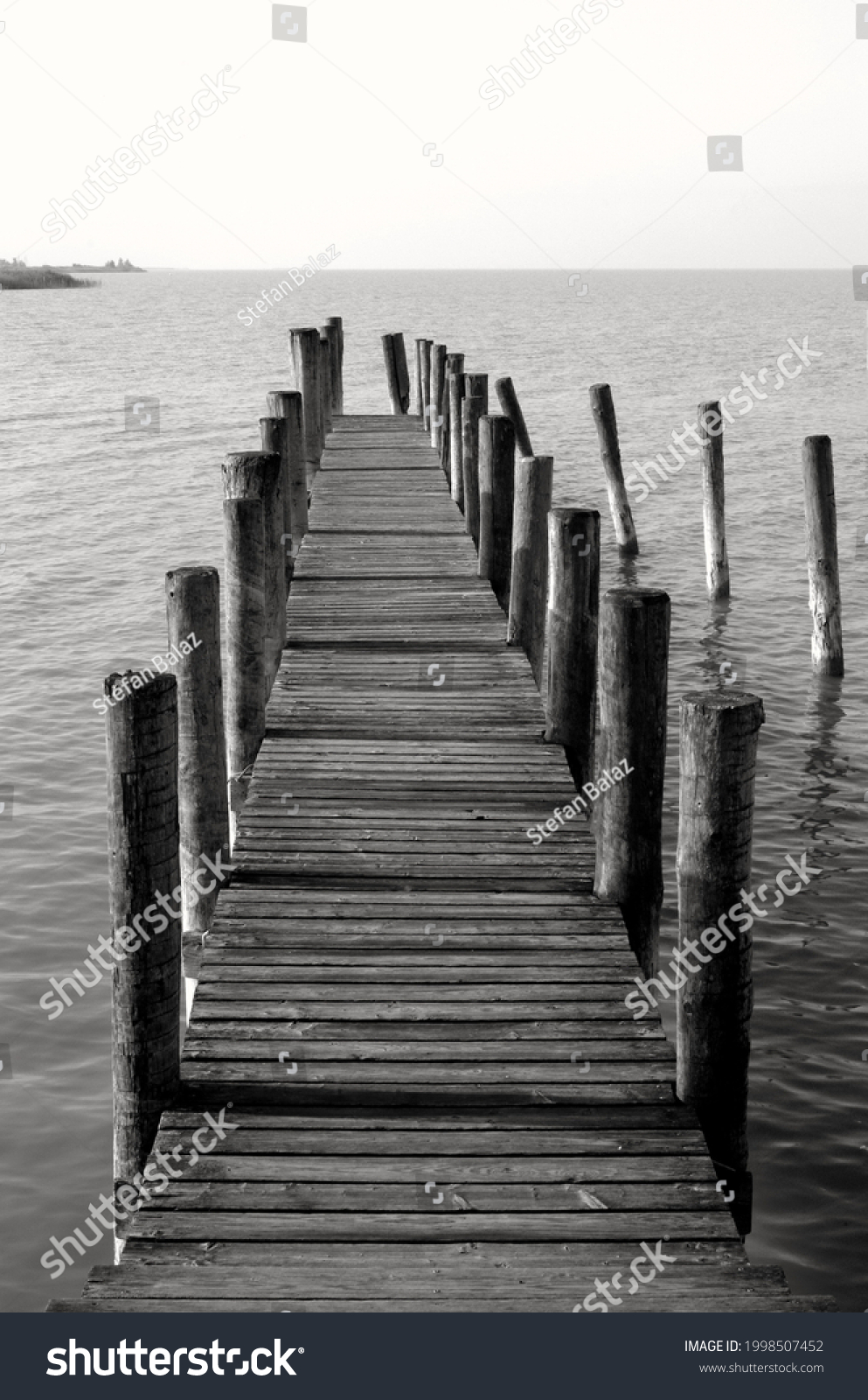 By the sea, beautiful view of a wooden pier, black and white photography. Wooden pier leading to the sea ocean or lake,boardwalk. Neusiedler See, Burgenland, Austria. #1998507452
