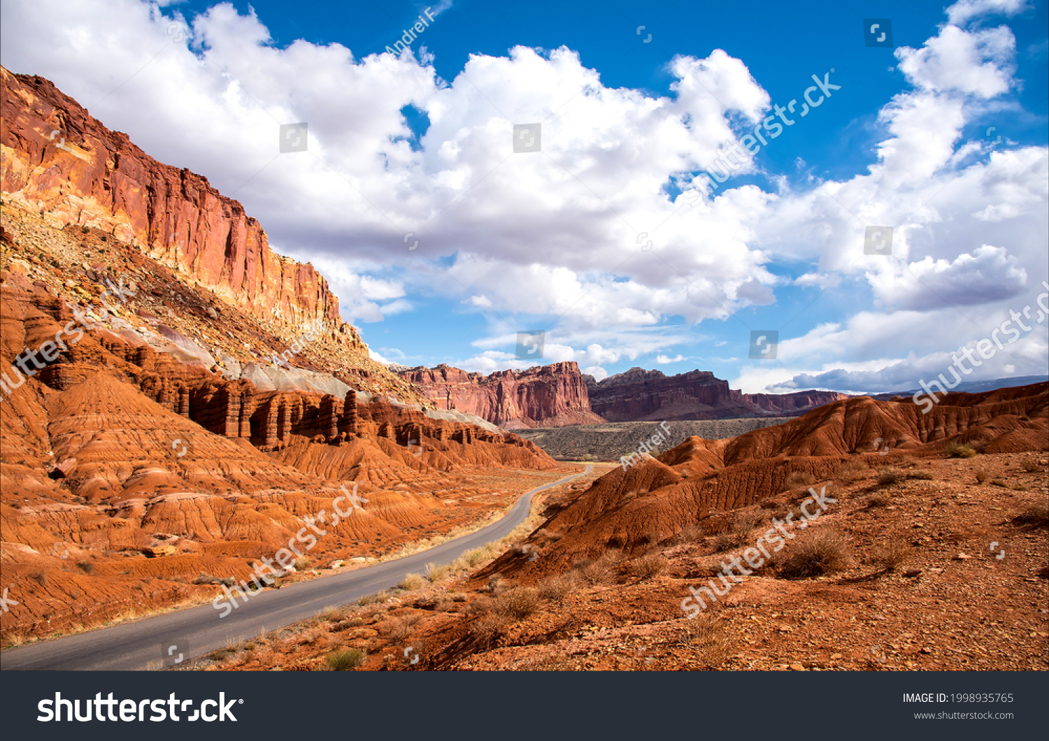The road through the canyon on a clear day. Red rock canyon road in mountains. Canyon road landscape. Mountain road panorama #1998935765