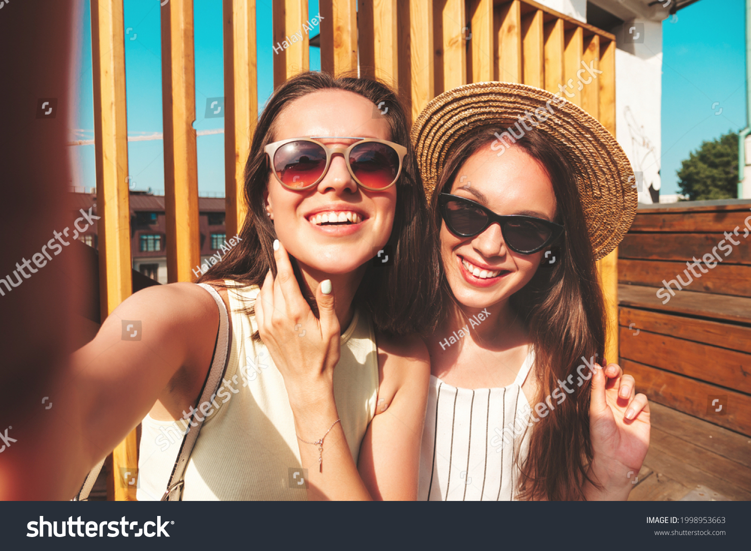 Two young beautiful smiling hipster female in trendy summer clothes.Sexy carefree women posing on the street background in hat. Positive pure models having fun at sunset, taking Pov selfie #1998953663