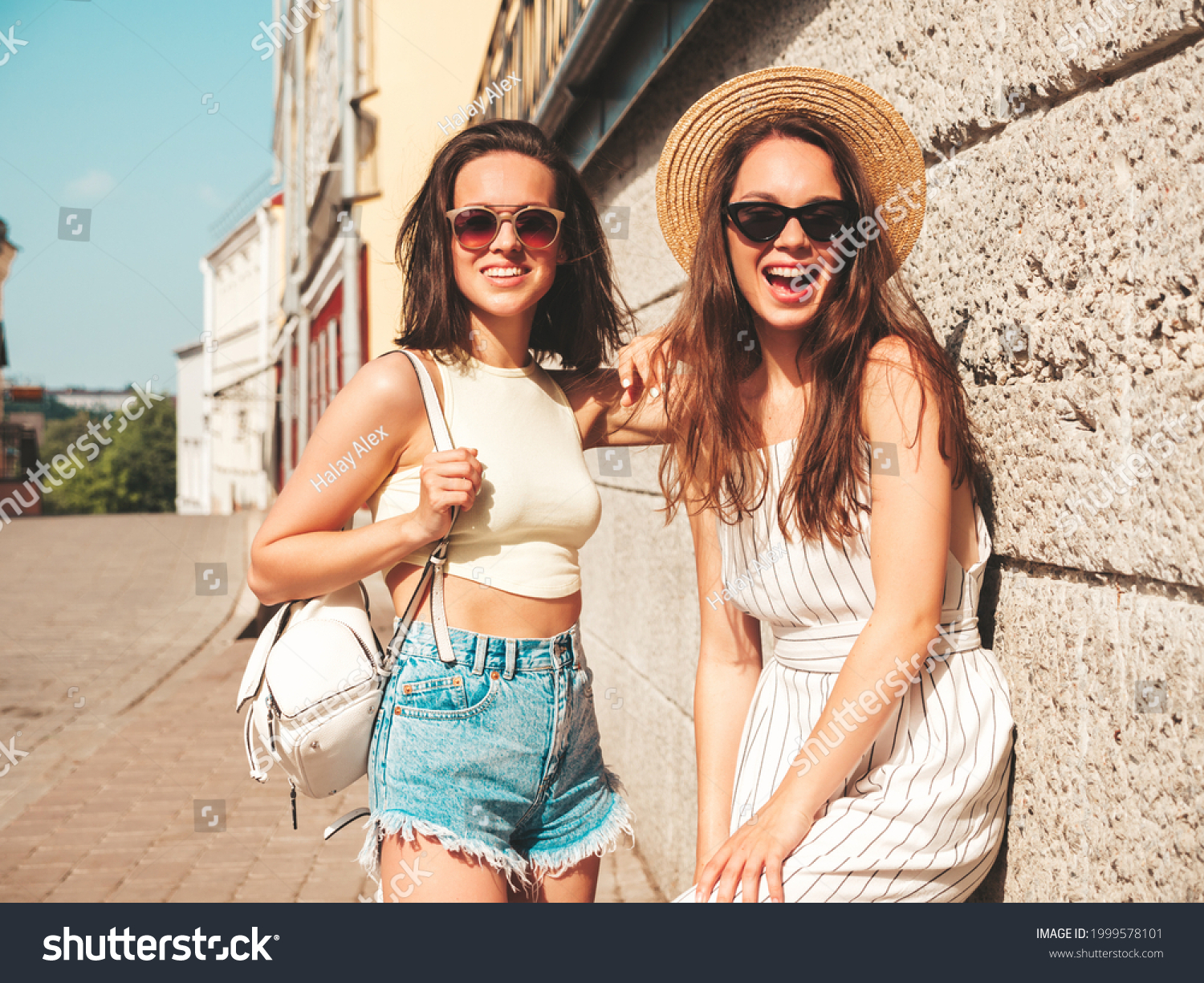 Two young beautiful smiling hipster female in trendy summer clothes.Sexy carefree women posing in the street near wall in hat. Positive pure models having fun at sunset, hugging  #1999578101