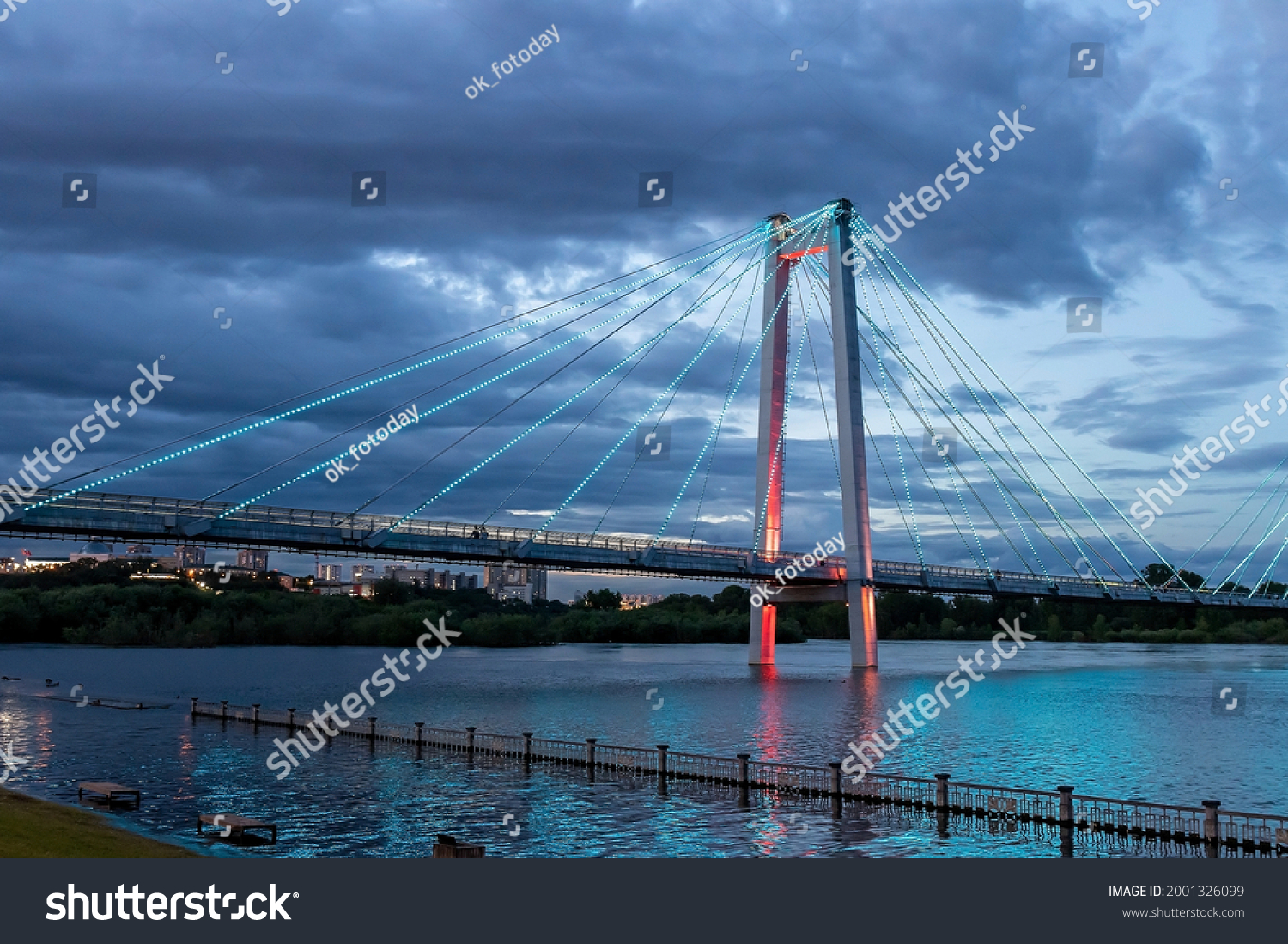 Night embankment, the area of the Vinogradovsky cable-stayed bridge: lowering the water level in the Yenisei during the flood. Russia, Krasnoyarsk, June 27, 2021