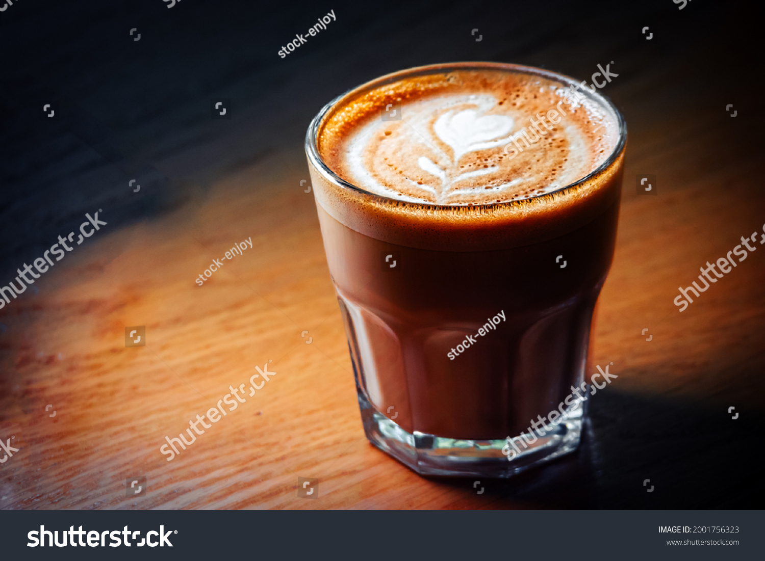 Flat-white coffee cup served on wooden table in spot of light, copyspace on left