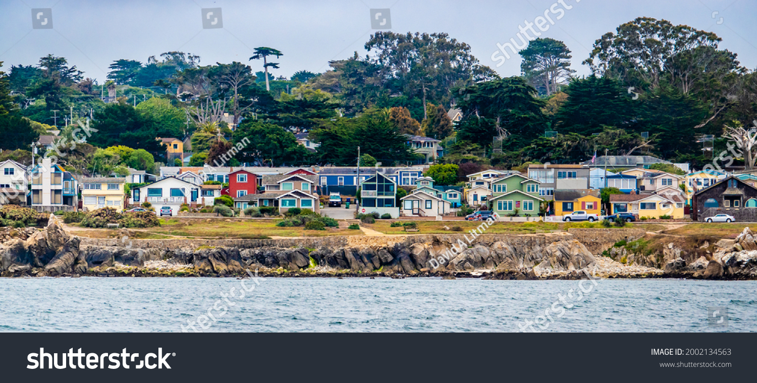 Houses in Pacific Grove, California (in Monterey County) overlook the rocky coastline, as viewed from a passing boat.