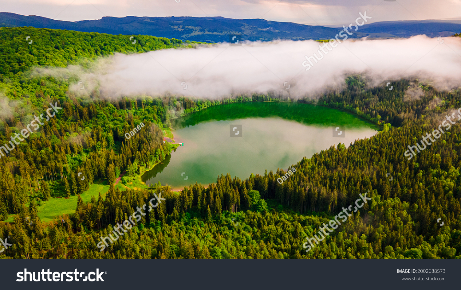 Aerial photography of Saint Ann volcanic lake located In Romania, Harghita county. Photography was taken from a drone at same altitude as the clouds from above the lake with camera angle lowerd.