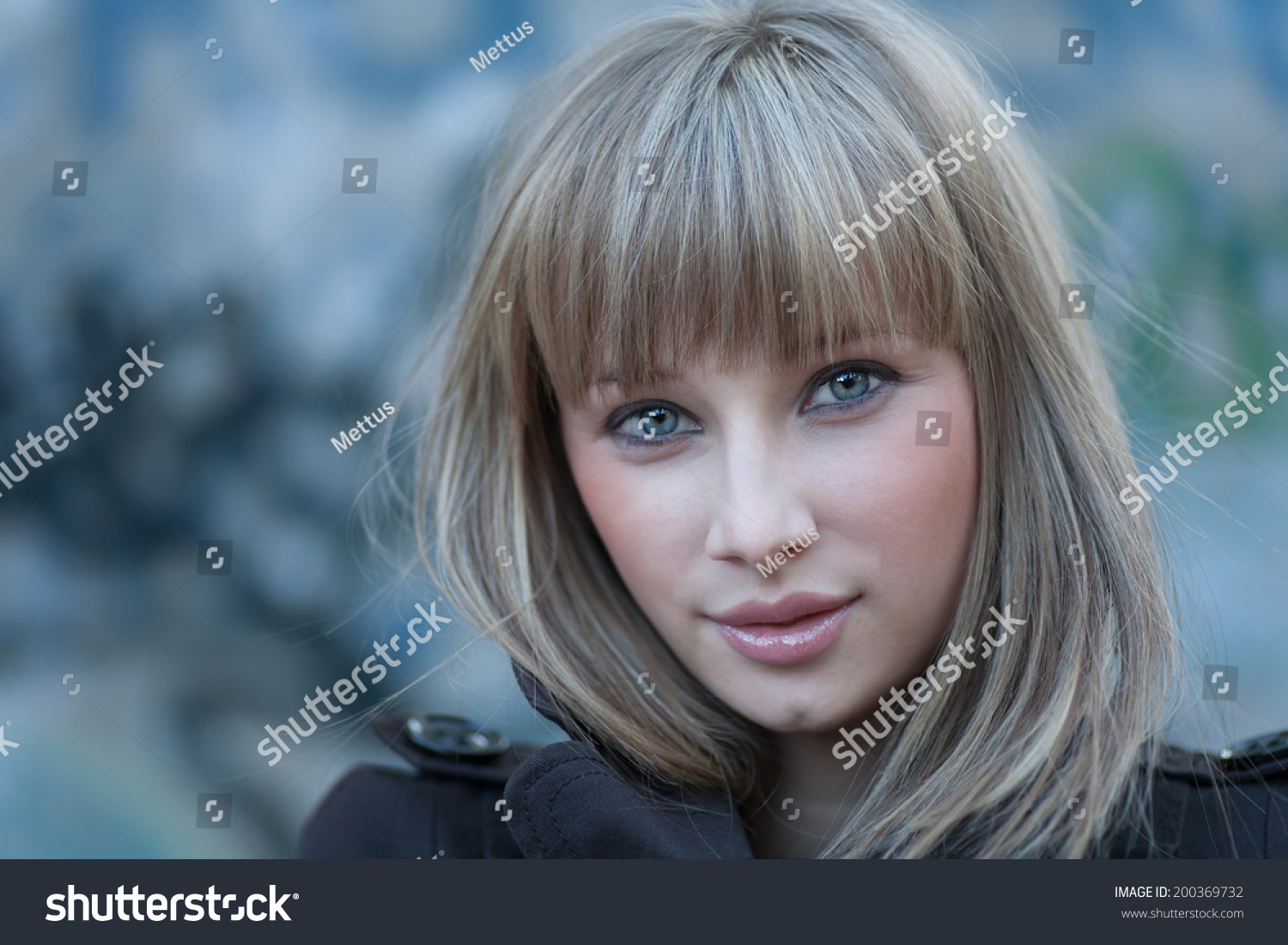 Charming blond haired women headshot against grungy wall. Cute blonde girl headshot in grungy settings. Young women portrait in slums front view. Solitude in the world