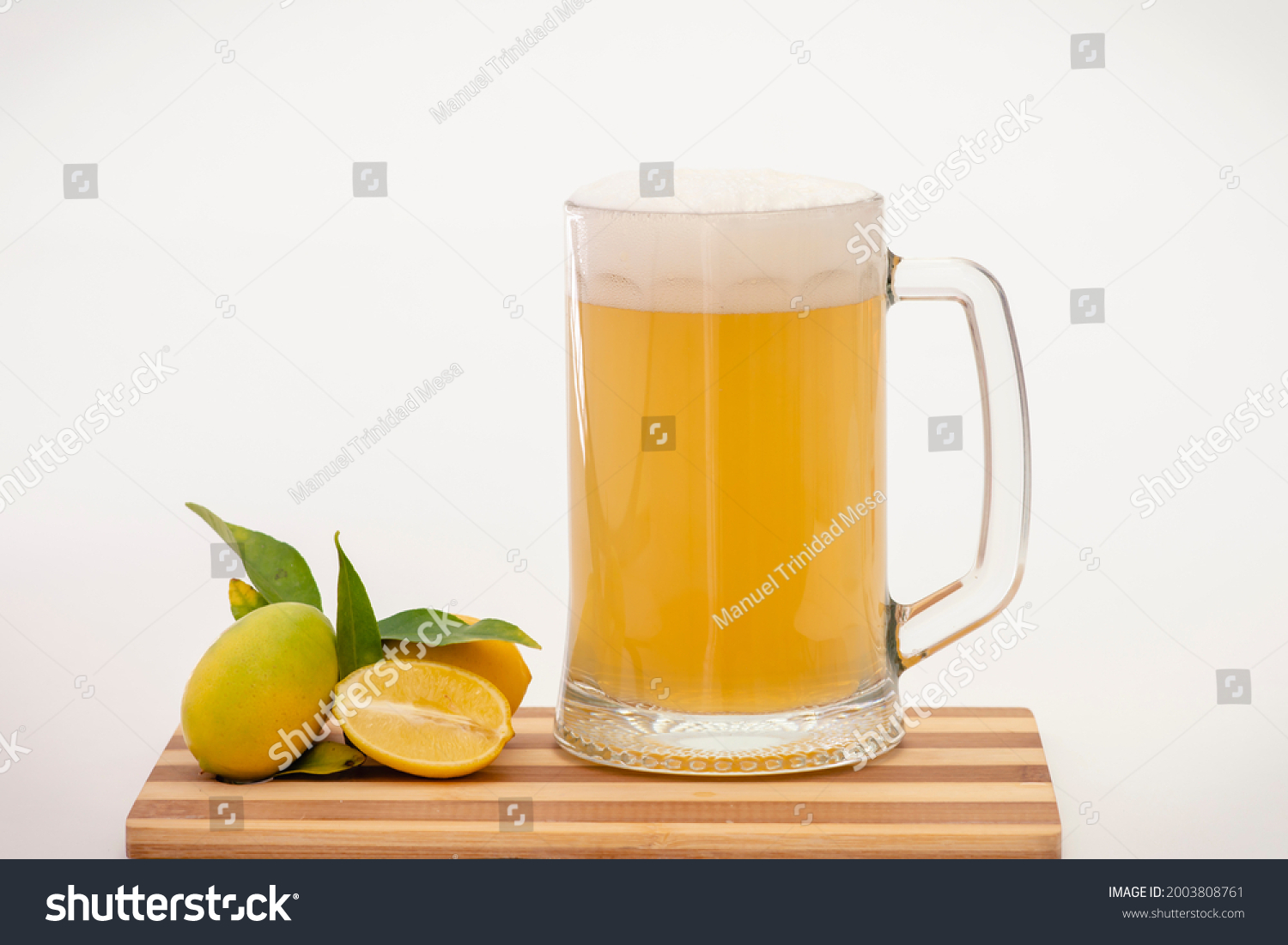 Beer mug with lemon soda and lemons with leaves, on a wooden board and white background