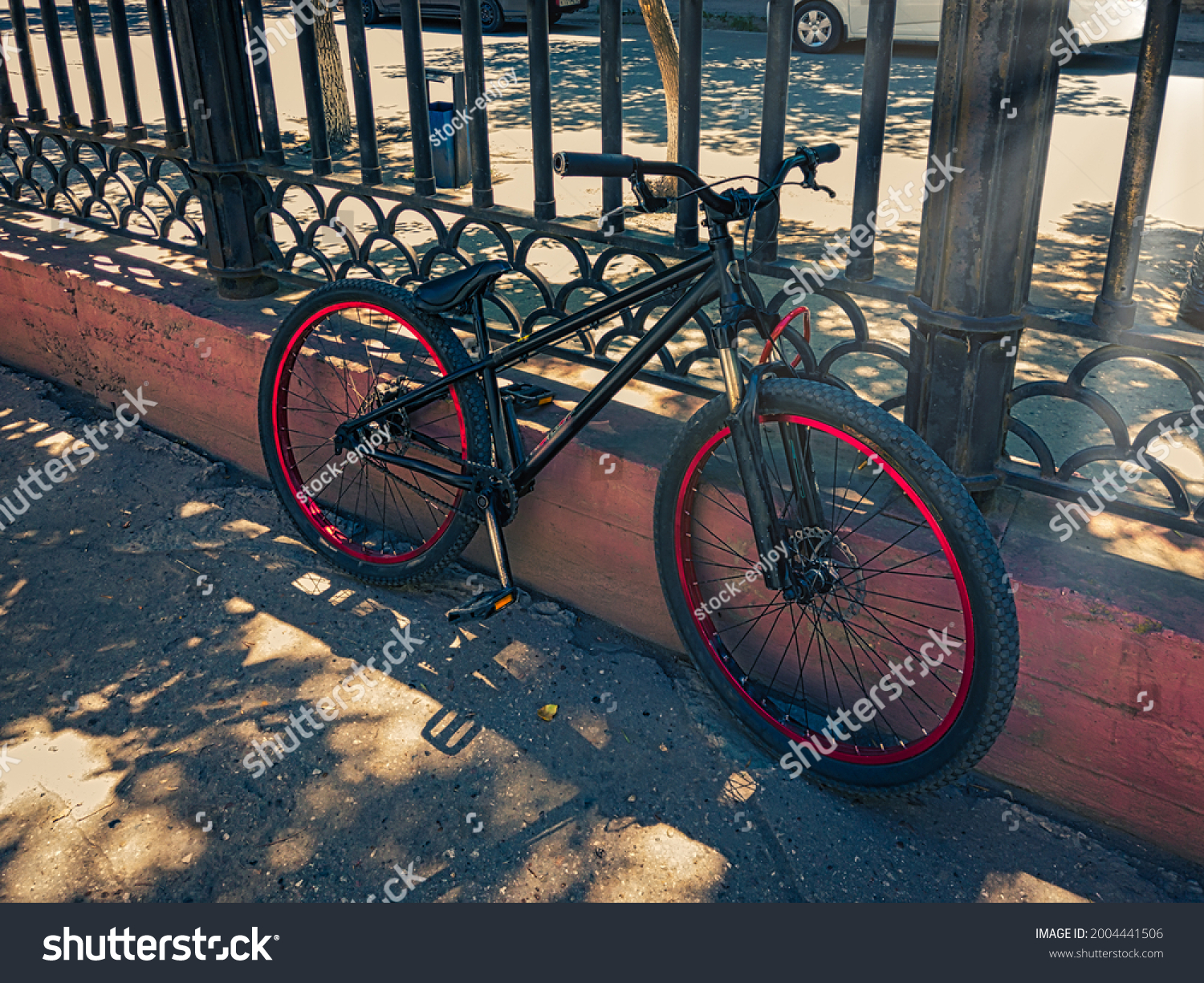 Urban transport. Black mountin bicycle parked against metal fence. Modern bicycle with lock parking in the city.