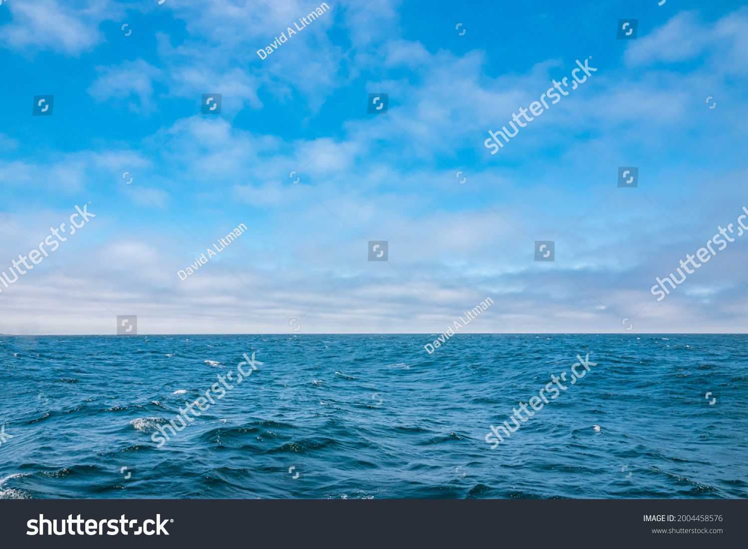 Colorful blue Pacific Ocean and partly cloudy sky background with copy space.