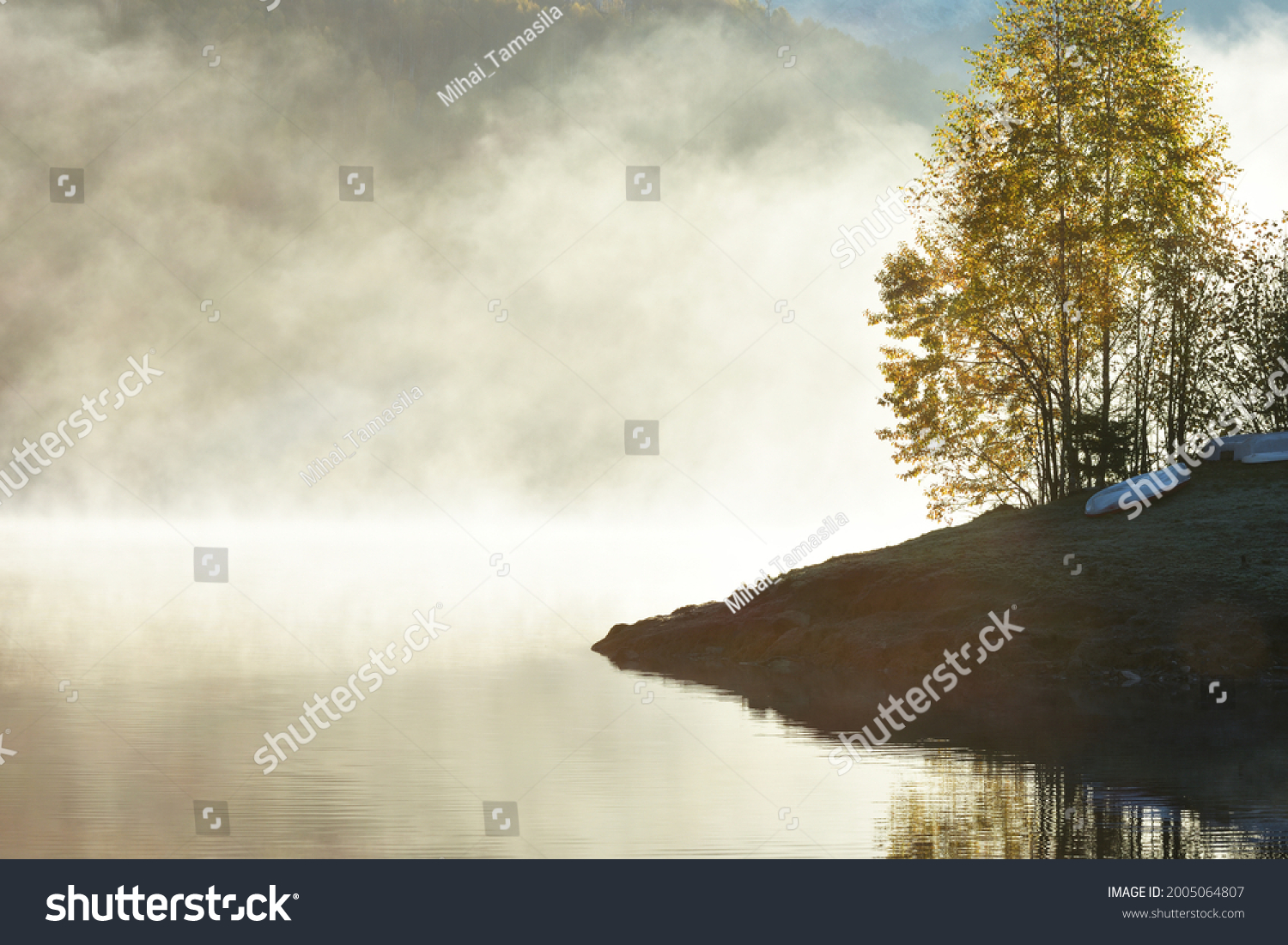 Fog covering the lake in autumn, forest reflection and sunlight