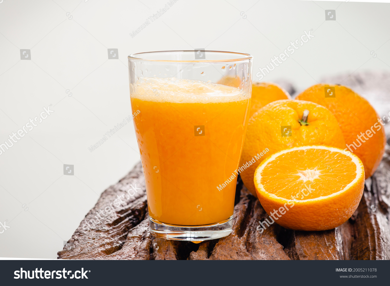 Oranges and juice on a rustic wood and white background
