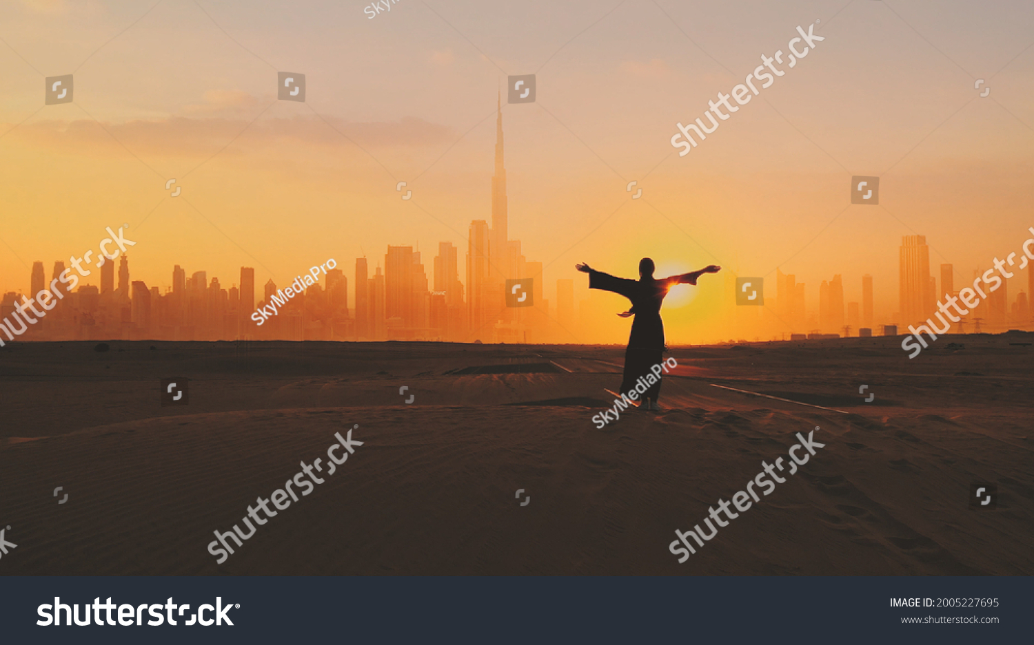 Arabic woman weared in traditional UAE dress - abayain rising her hands on the sunset at a desert with Dubai city silhouette on the background. #2005227695