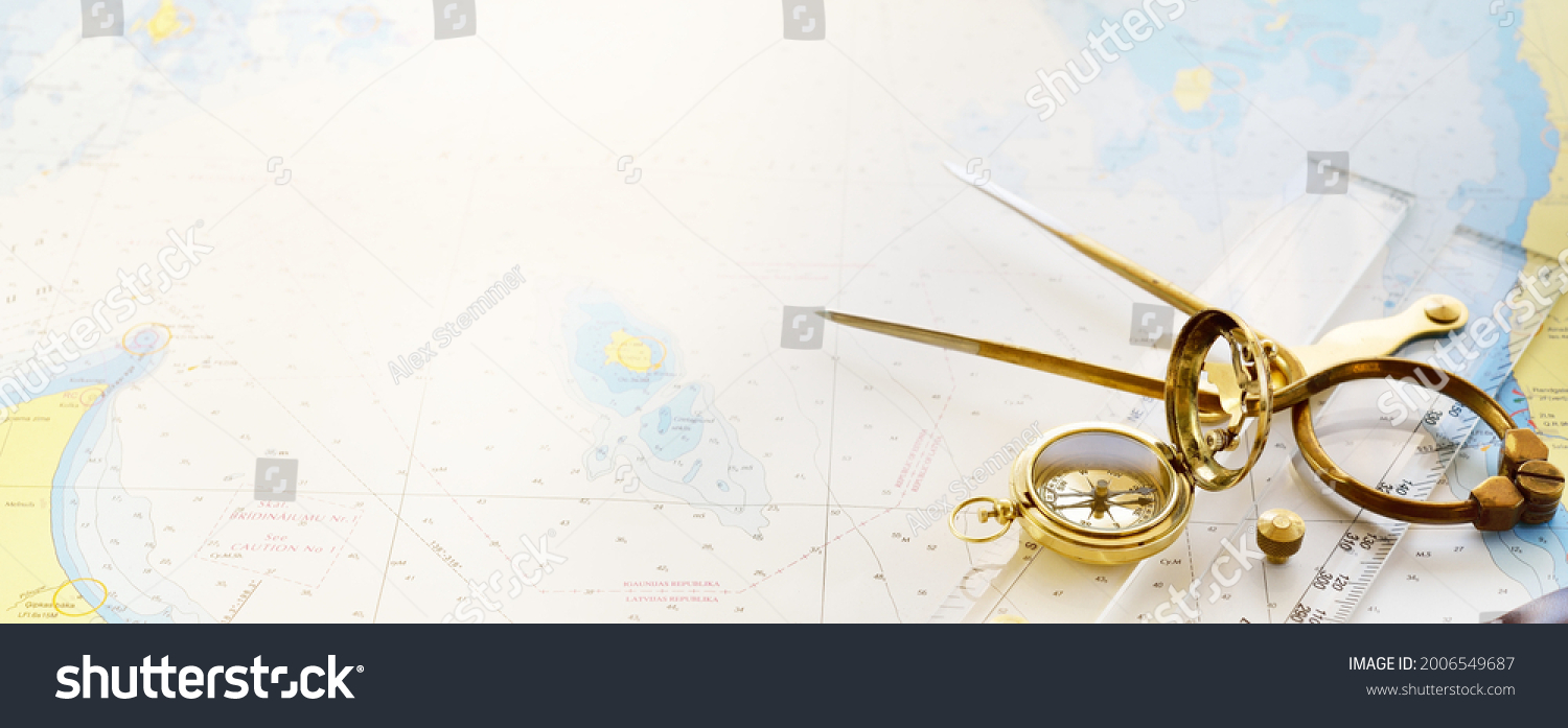 """Retro styled golden compass (sundial), antique vintage W HC 6"""" brass dividers calipers nautical navigation chart tool, parallel ruler, old white map close-up.   #2006549687"""
