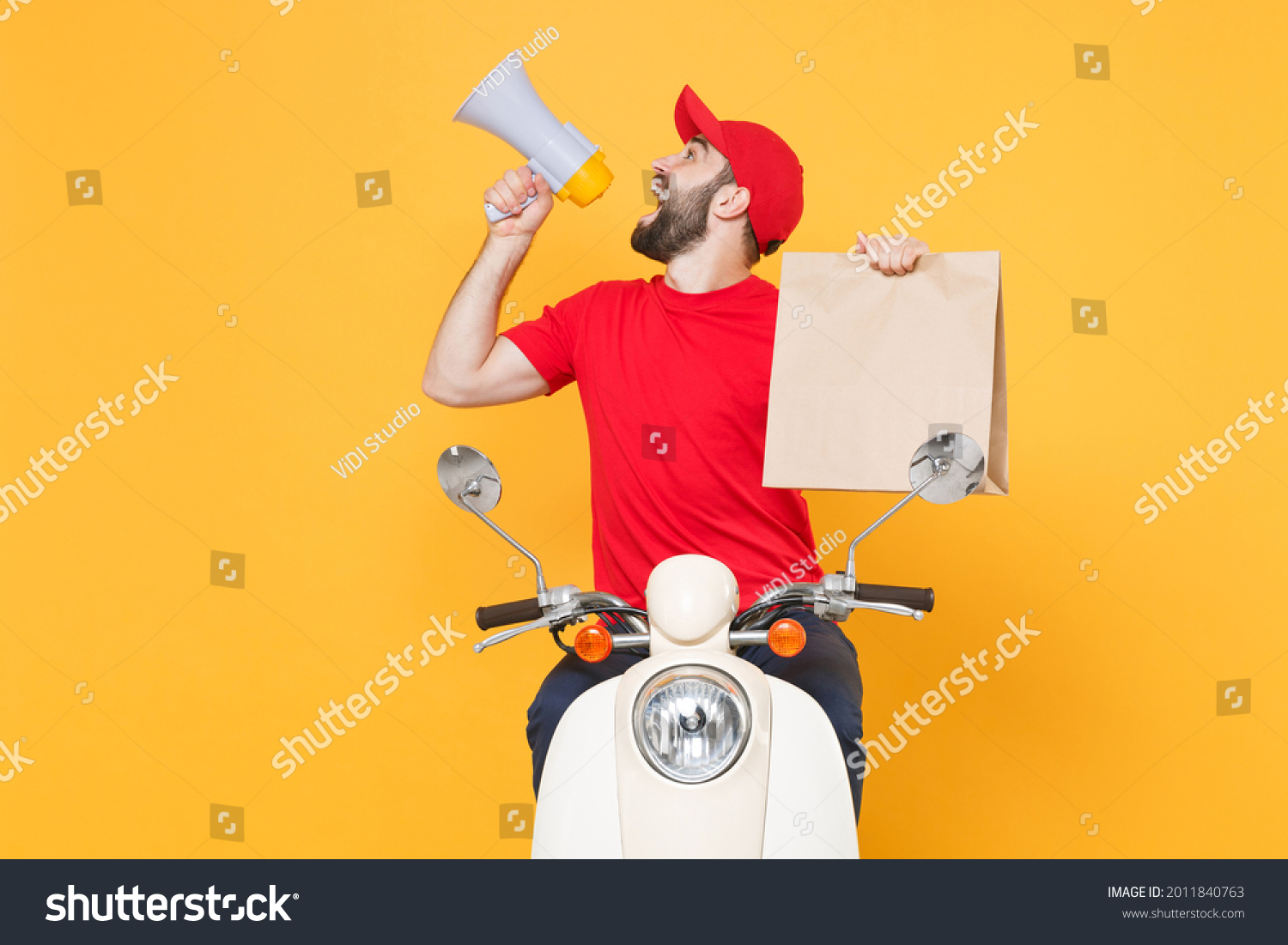 Delivery man in red cap t-shirt uniform driving moped motorbike scooter hold craft paper packet with food isolated on yellow background studio Guy employee working courier Service quarantine concept. #2011840763