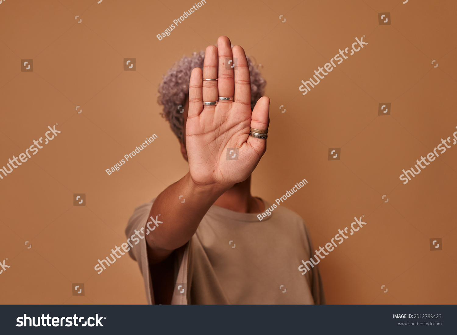 Serious African American woman covers herself with her palm, confidently shows prohibitory gesture stop and no signs shakes her head. Young ethnic woman against violence defends personal boundaries. #2012789423