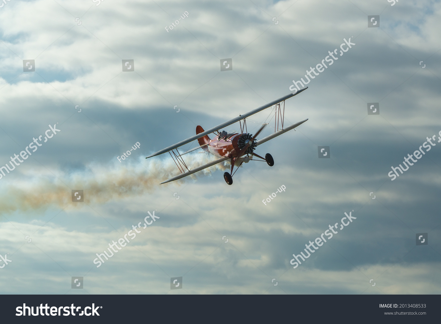 The historic red plane flies against the background of clumping clouds. #2013408533
