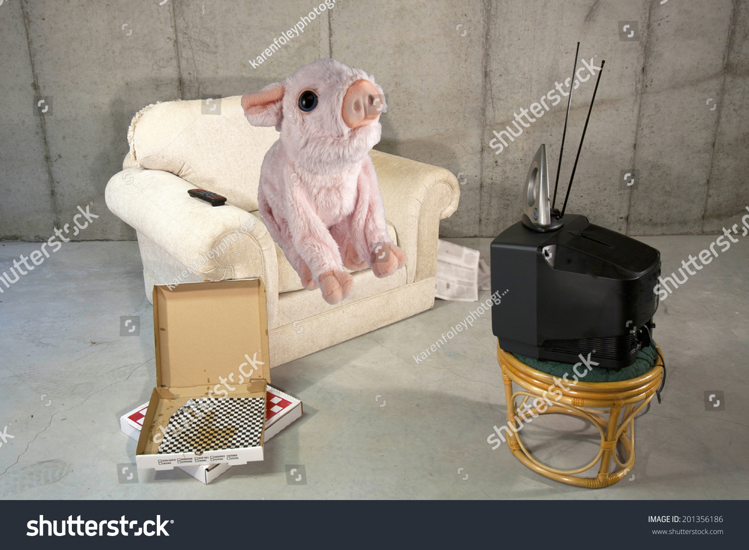 Pink pig sitting on an easy chair watching tv with empty for Sitting easy chairs