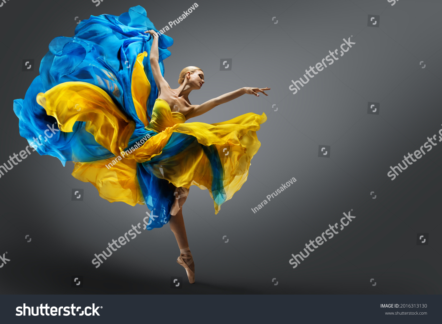 Beautiful Woman Ballet Dancer Jumping in Air in Colorful Fluttering Dress. Graceful Ballerina Dancing in Yellow Blue Gown over Gray Studio Background #2016313130