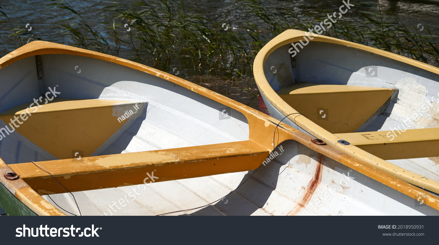 2 row boats side by side docked at a lake in summer. High quality photo #2018950931