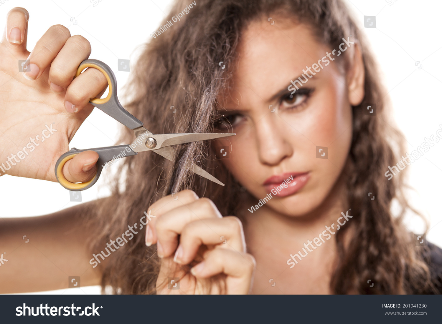 Nervous girl cuts her hair with scissors