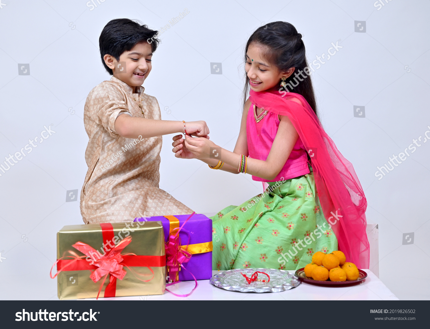Hindu Brother and sister  in ethnic wear holding Indian sweets and gift box on the occasion of Raksha Bandhan festival #2019826502