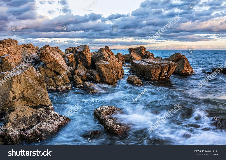 Waves beat against the coastal sea rocks. Coastal sea rocks. Sea rocks view #2022918431